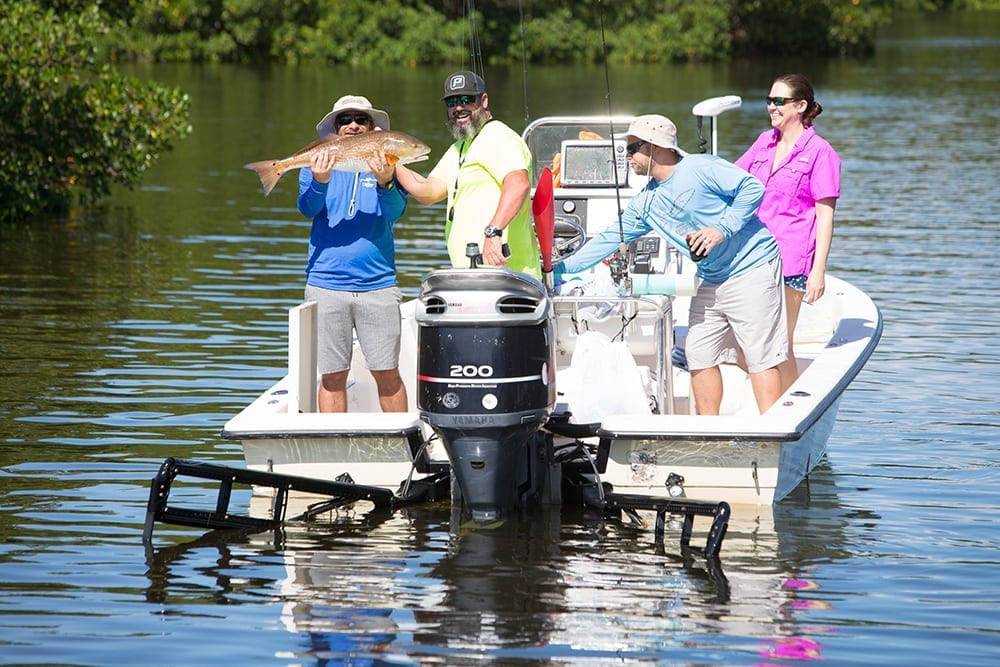 4 people on a boat in Tampa Bay near mangroves smiling and holding up a caught redfish