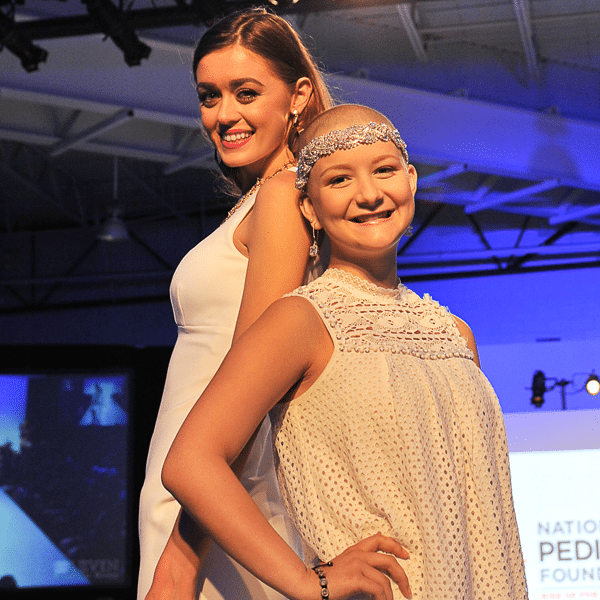 A female fashion model posing next to a young female cancer survivor at a runway event