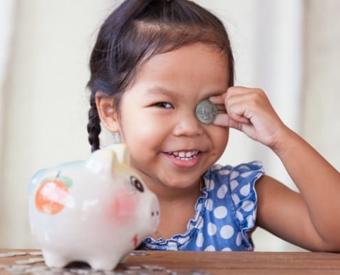 A little girl in front of her piggy bank smiling while holding up a quarter to her squinted eye