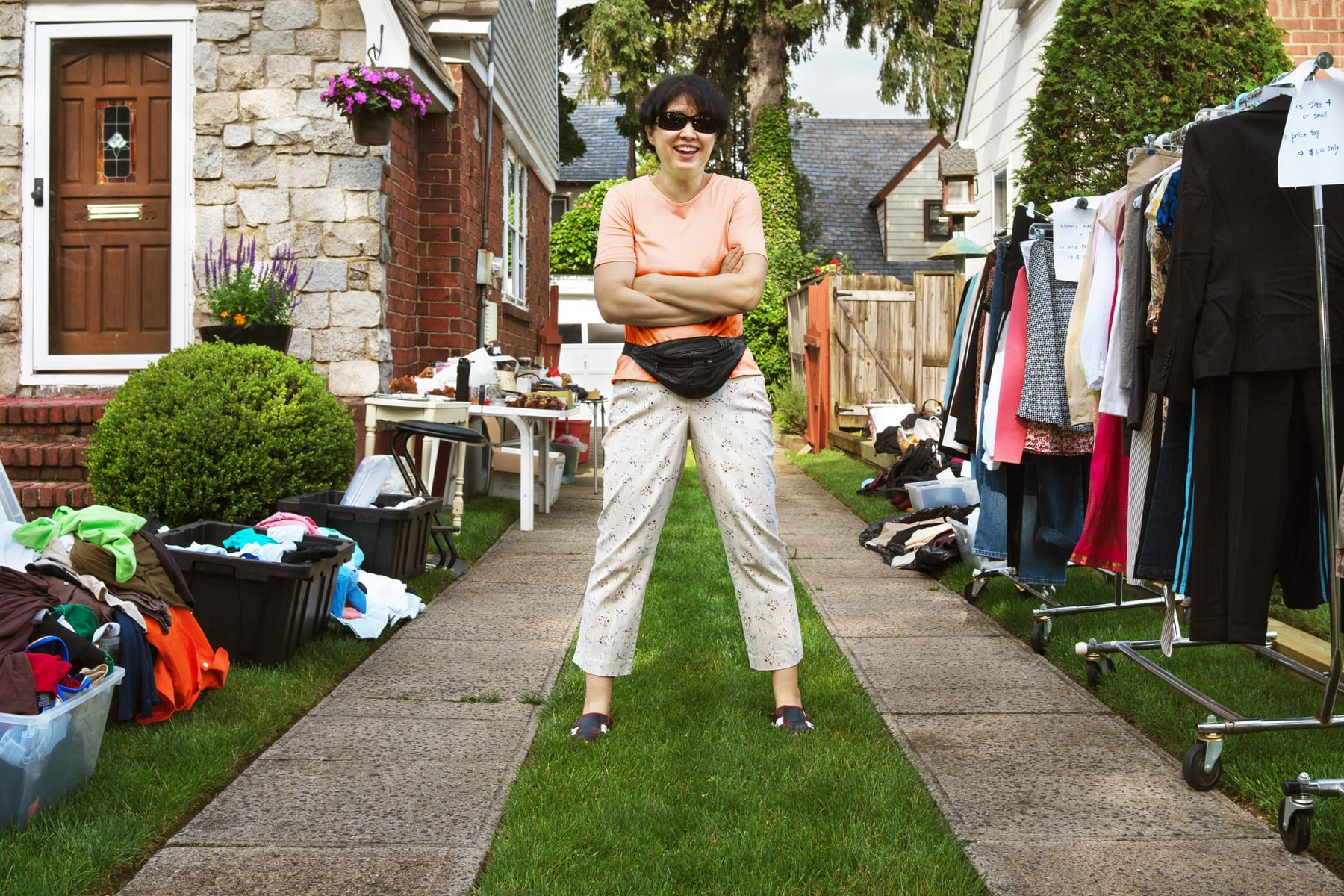 A smiling Mom standing with her arms crossed in her drive way after setting up her yard sale