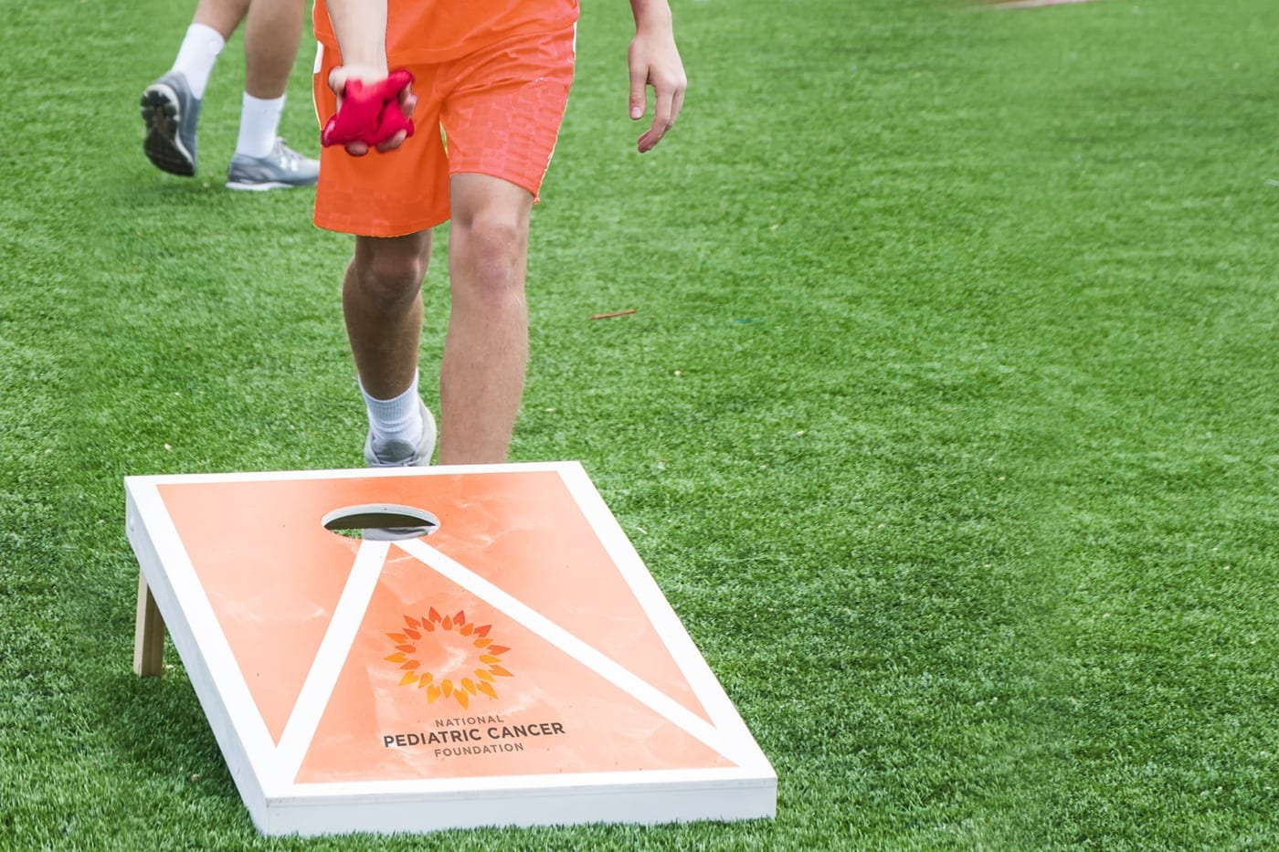 Boy standing behind a NPCF brand cord hole board ready to toss a bean bag