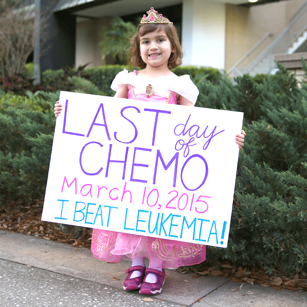 Little girl in princess outfit holding a sign saying last day of chemo and that she beat Leukemia