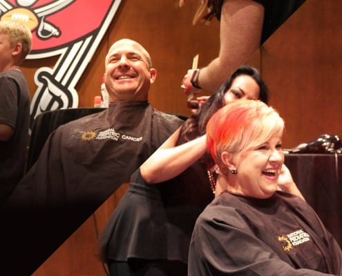 Picture cut in half showing one side a Male Tampa Bay Buccaneers Staff shaving his head and second half a Female Tampa Bay Buccaneers Staff coloring her hair