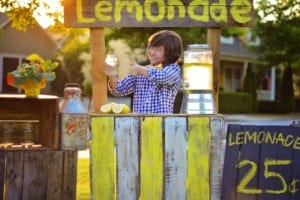 Young boy smiling holding up a glass of lemonade at his lemonade stand