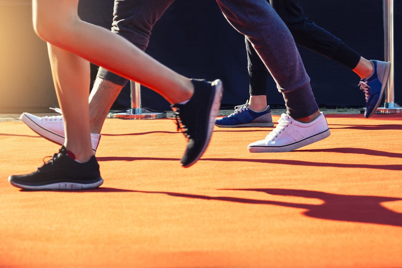 Picture of peoples from the waist down walk on orange track