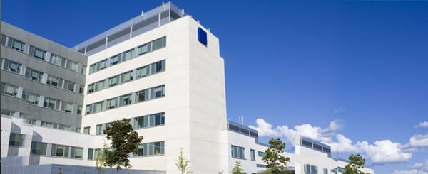 Picture of the outside of a hospital with bright blue sky