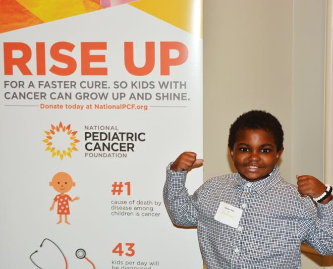 Picture of young African American boy flexing his muscles showing how strong he is to beat cancer