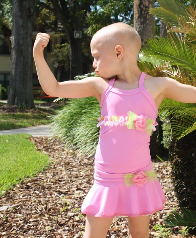 Picture of young little girl in pink ballerina outfit flexing to kiss her bicep so that she is strong and can beat cancer