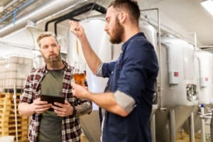 Two men with pipette testing craft beer at brewery