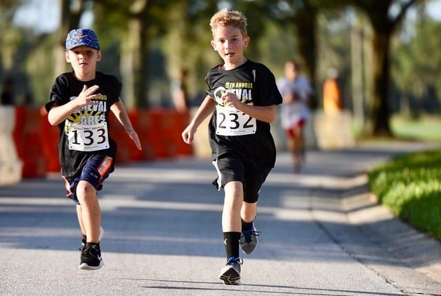 Two young boys are competing in the Cheval Cares 5K in Lutz Florida as they are running fast towards the finish line