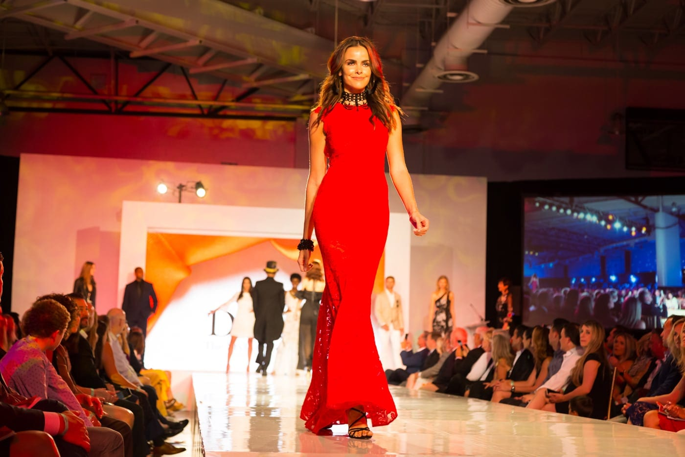 Woman in red dressing walking down the runway at a National Pediatric Cancer Foundation Fashion Event