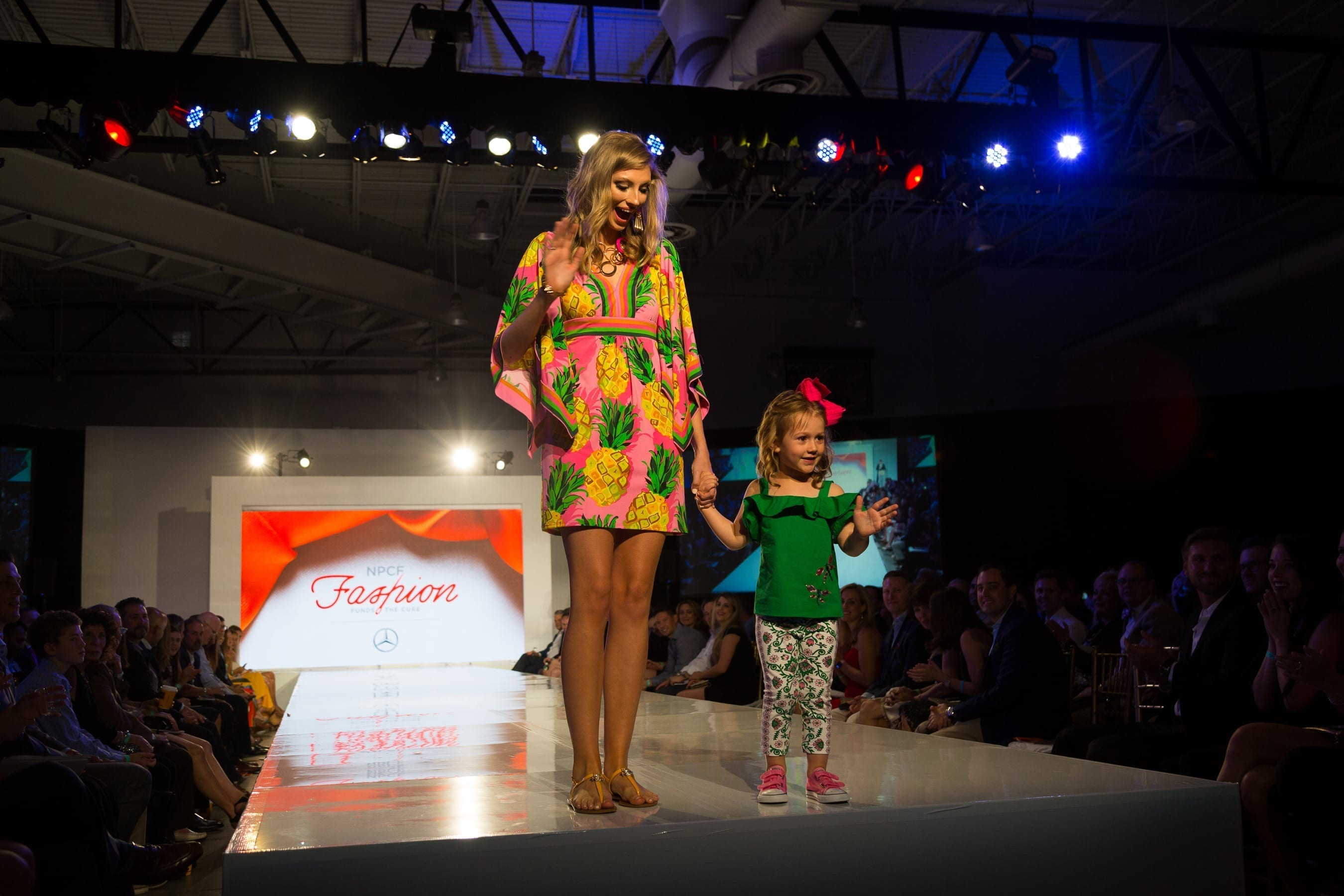 Young pediatric cancer patient walking the runway and waving at the crowd at the National Pediatric Cancer Foundation Fashion Funds the Cure Event in Tampa FL