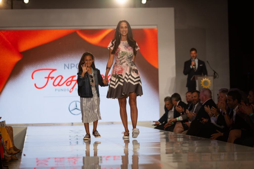 Young pediatric cancer girl walks the runway with a professional Dillards model at the National Pediatric Cancer Foundation Fashion Funds the Cure Event