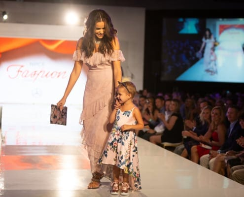 Picture of Female Model with little girl walking down a NPCF Fashion Event runway