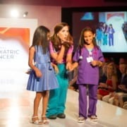 A girl cancer patient walks the runway with her registered nurse as she dreams of being an oncologist when she grows up she is participating in the Dream Walk