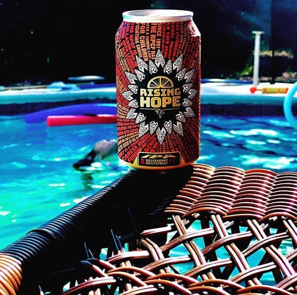Can of Rising Hope on top of chair with swimming pool in the background