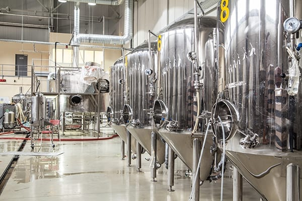 Inside a brewery plant with brewering kettles tubes and tanks made of stainless steel