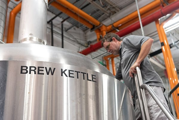 Man about to pull a sample of Rising Hope out of a stainless steel brew kettle
