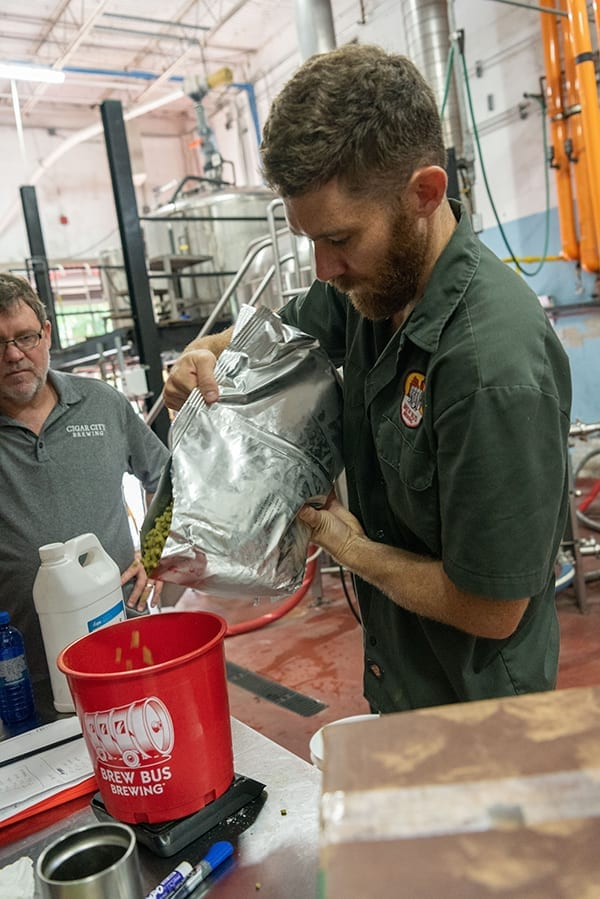 Man pouring hops into a red Brew Bus Brewing bucket