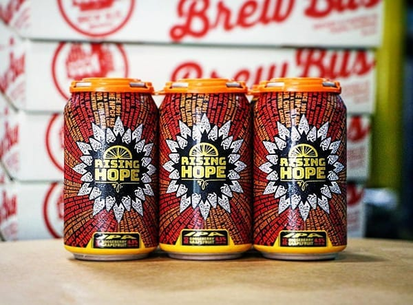 Picture of 3 Rising Hope cans with Brew Bus packaging behind them