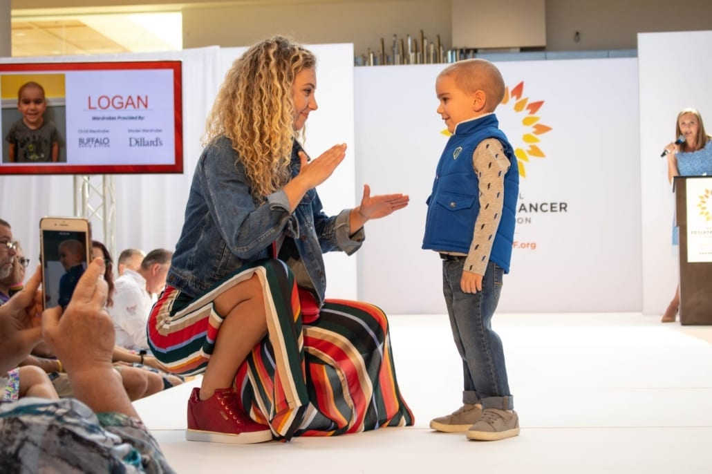 Logan Walking with a model at Fashion Funds the Cure