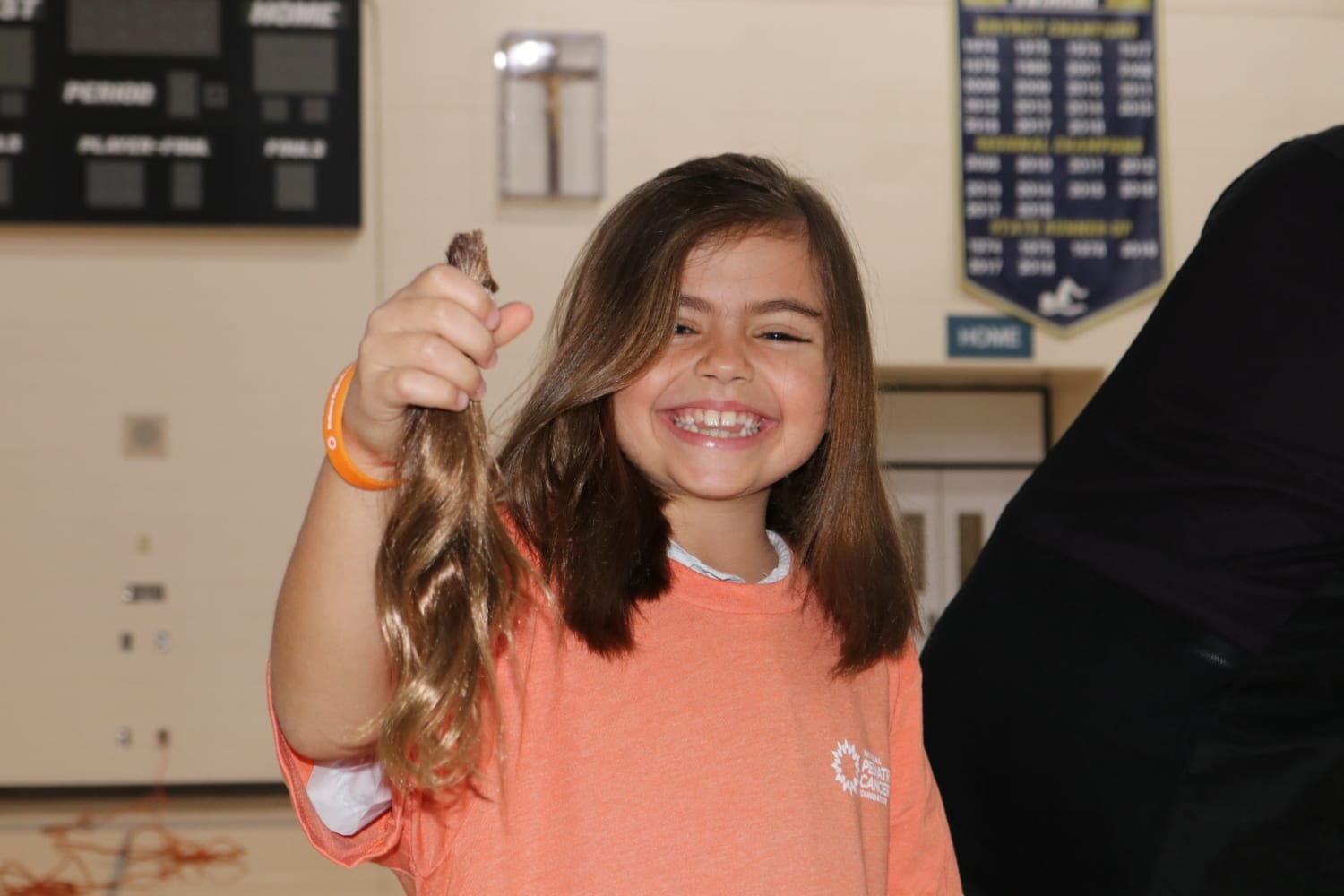 Young girl shows off her hair after it was cut off at the National Pediatric Cancer Foundation's Cut and Color Funds the Cure with the Academy of Holy Names in Tampa, Florida